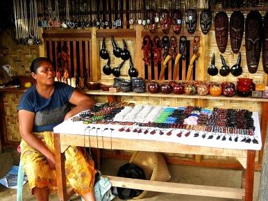Seorang ibu menunggui jualan pernak-pernik kerajinan warga lokal