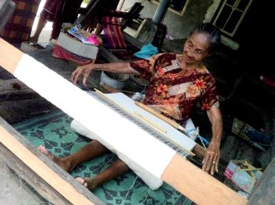 Seorang nenek di Bayan sedang tekun menenun kain