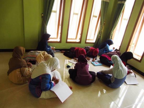 Santriwati asyik menulis duduk senyaman mereka